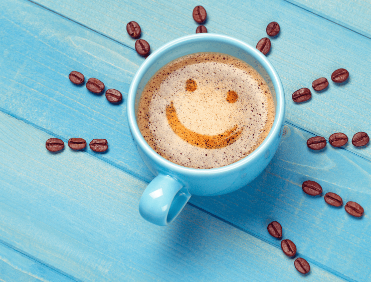 Kaffeetasse mit Smiley auf dem Kaffee und rundherum Kaffeebohnen als Sonnenstrahlen für bessere Laune