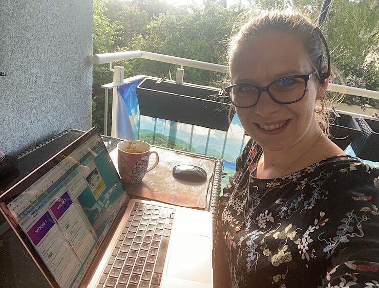Petra Prinz lächelt in die Kamera und zeigt sich beim Bloggen mit MacBook am Balkon