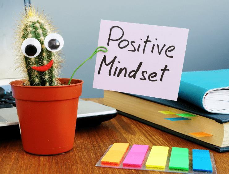 """positive Lebenseinstellung - links ein Blumentopf mit Kaktus, rechts ein Post it mit dem Wortlaut """"Positive Mindset"""" und drunter kleine bunte Post its"""
